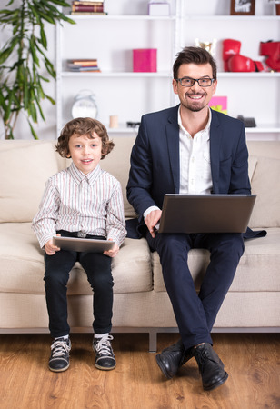 Portrait of a young father in suit and his son with laptop. photo