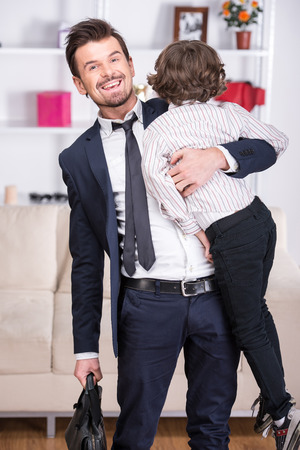 Little son meets his businessman father from work. photo