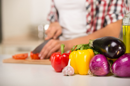 Close-up hands of a woman who cuts vegetables. Focus on the vegetables on the table. photo