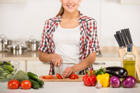 Young woman is chopping vegetables in the kitchen. photo