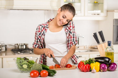 Young woman is chopping vegetables in the kitchen and speaking by phone. photo
