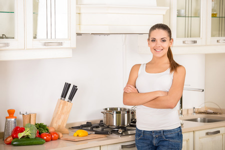 Young, smiling woman in the kitchen while cooking dinner. photo