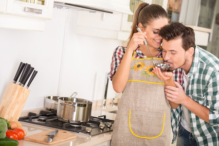 Young happy couple in the kitchen while cooking dinner.