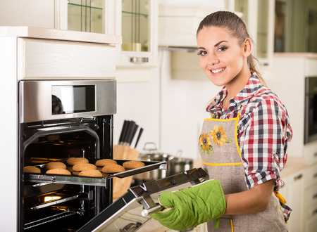 Young beautiful woman pulls cookies from the oven. photo