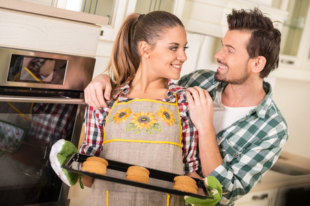 Beautiful woman is holding hot roasting pan with cookies, and looking at her happy husband. photo