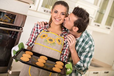 Beautiful woman is holding hot roasting pan with cookies. Happy husband is kissing her. photo