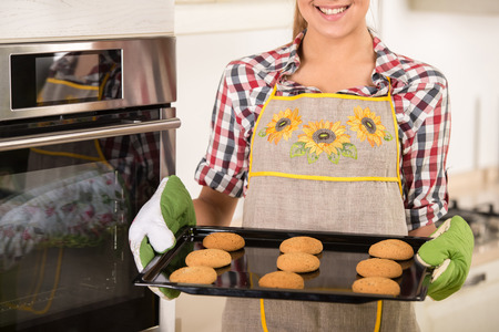 Young woman is holding hot roasting pan with cookies, in the kitchen. photo