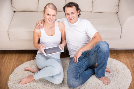 Portrait of a happy young couple with tablet at home. photo