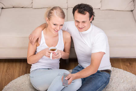 Young couple are spending time together. They drink tea and watch TV. photo