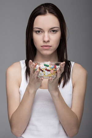 phial: Portrait of a young woman with pills in a glass phial on gray background. Stock Photo