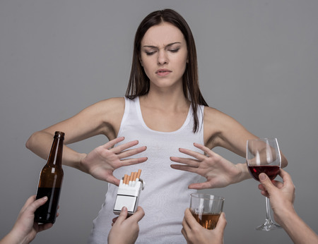 Portret van een jonge vrouw die naar alcohol en tabak weigert. Jong meisje worstelt met haar slechte gewoonten.
