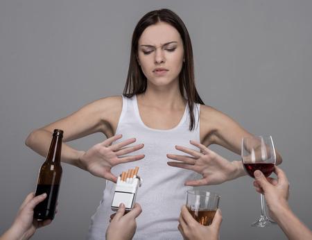 Retrato de uma jovem mulher que se recusa a álcool e tabaco. Moça que esforça-se com seus hábitos maus.