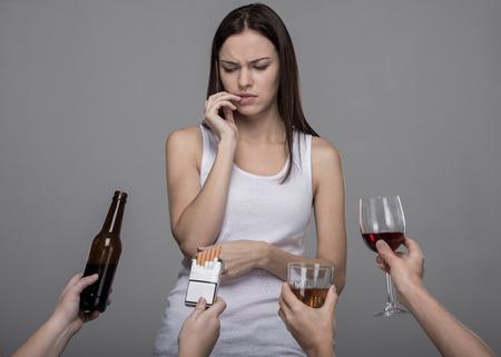 アルコールやタバコを拒否した若い女性の肖像画。若い女の子は彼女の悪い習慣と苦労しています。