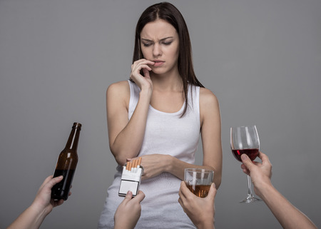 Portrait of a young woman who refuses to alcohol and tobacco. Young girl struggling with her bad habits.