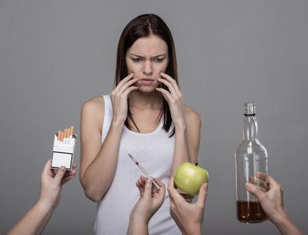 malos habitos: Concepto de malos h�bitos. Una joven mujer, alcohol, drogas, tabaco. Chica joven que lucha con sus malos h�bitos. Foto de archivo