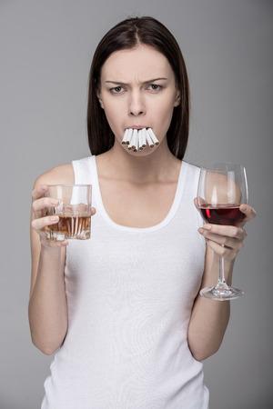 malos habitos: Concepto de malos h�bitos. Una joven mujer, el alcohol, el tabaco.