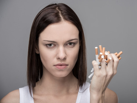 quit smoking: Young woman with many cigarettes. Concept of quit smoking. Stock Photo