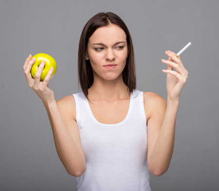 Difficult choice. Young woman with apple and cigarette. photo