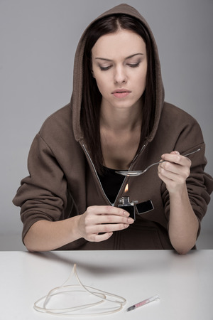 oncept: Young woman with syringe and drugs. Ð¡oncept of addiction. Stock Photo