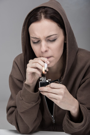 Young woman is smoking drugs, on the gray background. photo