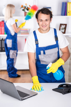 Young couple professional cleaners are cleaning the office. photo