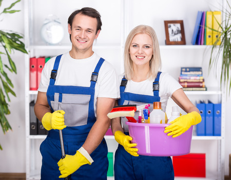 cleaning background: Young smiling couple are holding cleaning tools. Stock Photo