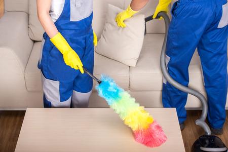Limpiadores profesionales pareja joven están limpiando la casa.