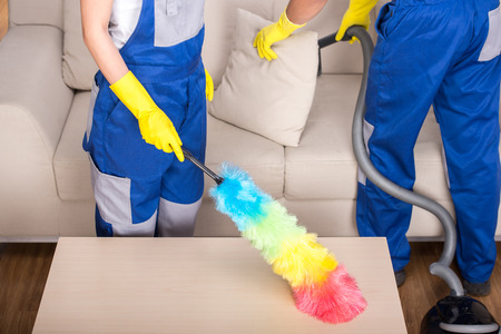 cleaning background: Young couple professional cleaners are cleaning the house. Stock Photo
