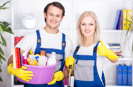 Young smiling couple are holding cleaning tools. photo