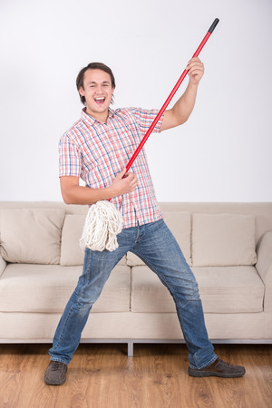 Funny man is mopping floor and playing music using mop. photo