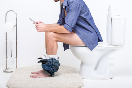 Businessman is working with digital tablet while sitting on the toilet. Stock Photo