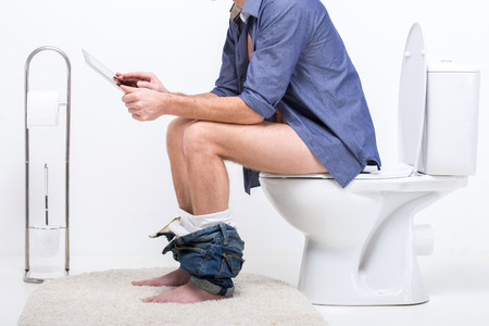bathrooms: Businessman is working with digital tablet while sitting on the toilet. Stock Photo