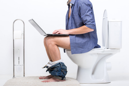 water closet: Businessman is working with laptop while sitting on the toilet.