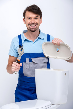 Plumber is repairing a flush toilet, on white background. photo