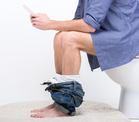 black bathroom: Businessman is working with digital tablet while sitting on the toilet. Stock Photo