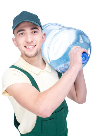 delivery man: Water delivery courier is holding a bottle on his shoulder. Stock Photo