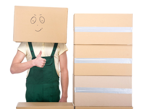 Delivery man with a lot of boxes and cardboard box on his head with smiley face. photo