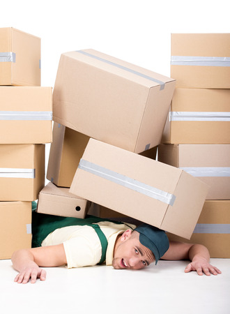 A lot of cardboard boxes fell on a young man. photo
