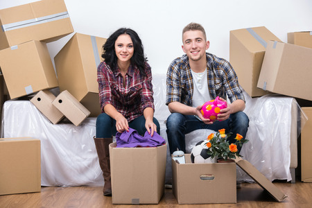 Couple are moving into a new home and unpacking boxes.