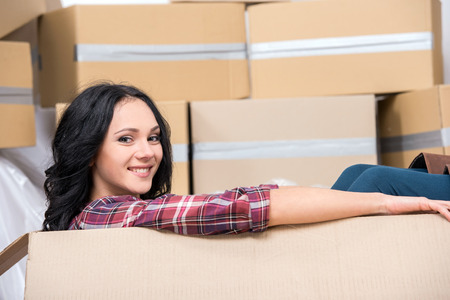 woman sitting on floor: Young woman in new apartment in a cardboard box is looking at the camera.