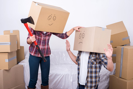 Cheerful young couple with cardboard boxes on their heads. A woman holds an ax. photo