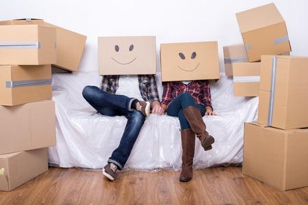 笑顔の顔と頭の上の段ボール箱とのカップルは、家を移動の後床に座っています。 写真素材