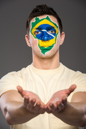 Portrait of young man with brazilian flag painted on his face. photo