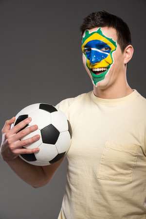 Portrait of young man with soccer ball and brazilian flag painted on his face. photo