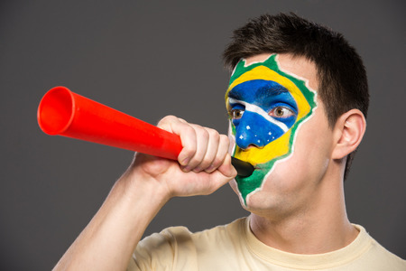Portrait of young man with vuvuzela and brazilian flag painted on his face. photo