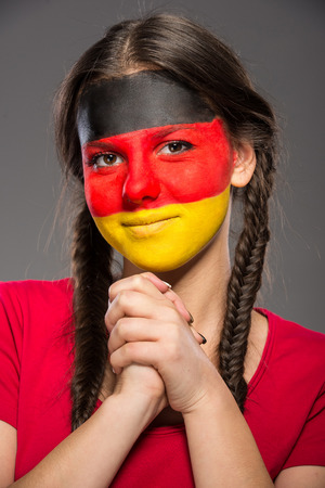 Flag of Germany painted on a face of a young woman. photo