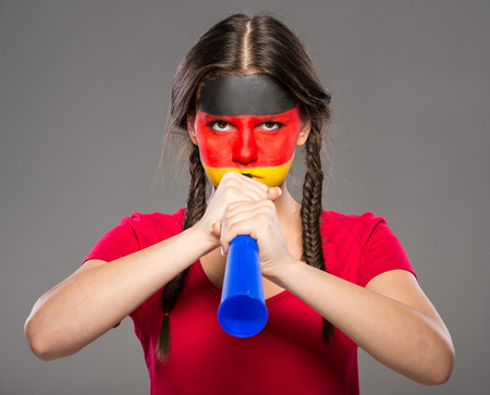 vuvuzela: Flag of Germany painted on a face of a young woman with vuvuzela.