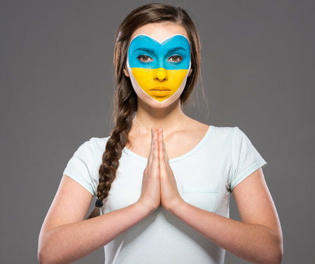 Flag of Ukraine painted on the face of the young beautiful woman. photo