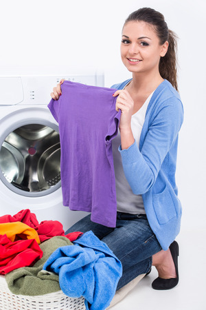 Happy young woman is doing laundry with washing machine at home. photo