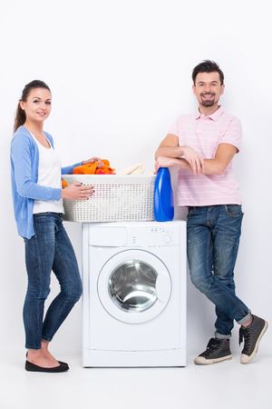 man laundry: Housework. Young woman and man are doing laundry and looking at the camera.